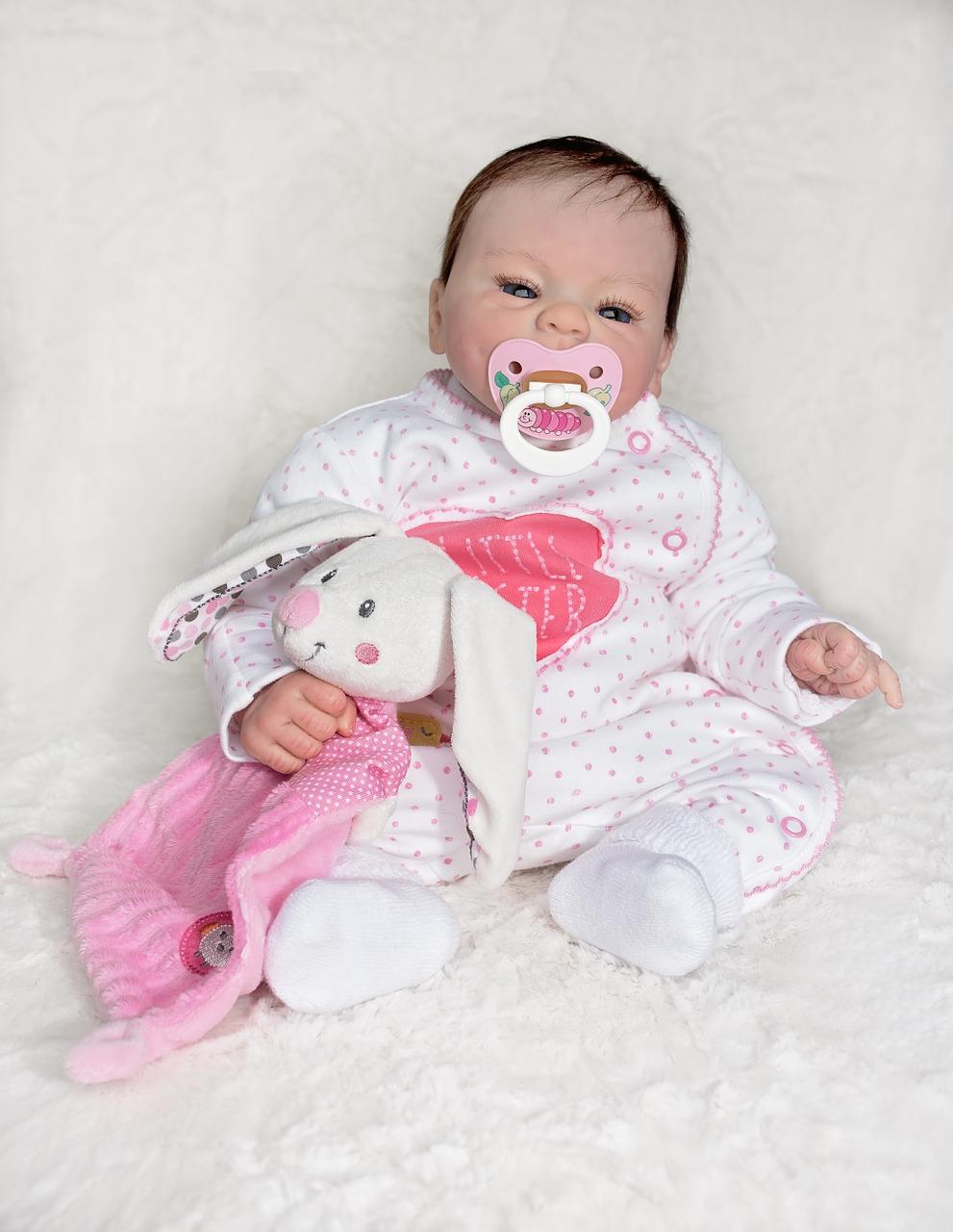 Cette poupée reborn a un doudou rose.